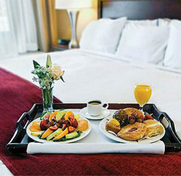 Breakfast tray with flowers, orange juice, a hot beverage and 2 plates of fruit and croissants on made bed.