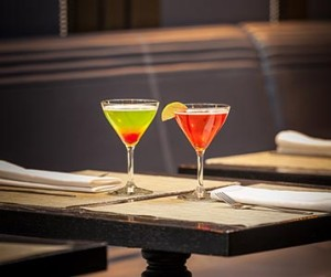 Two cocktail glasses on a dark marble table. Green and red cocktail on the left, blood orange cocktail on the right.