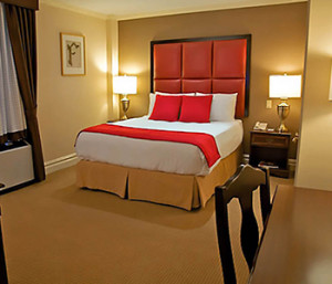 Brightly lit Fitzpatrick Deluxe Room with triple-sheeted beds, red accent pillows and leather headboard.