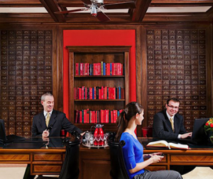 Smiling Fitzpatrick Hotel staff in front of book case assisting female guest to check-in.