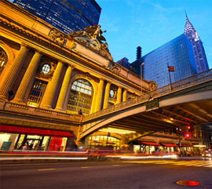Exterior of Grand Central Terminal with bridge and skyscrapers in view at night time.