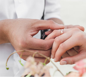 Wedded couples hands with gold wedding band on woman's finger and blurred flora in the foreground.