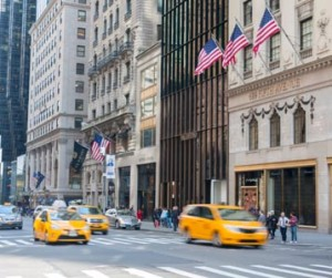 Street view of the exterior of the Prada store on 5th Avenue with yellow cabs driving past.