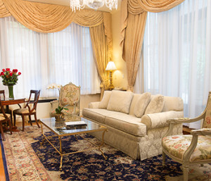 Brightly lit Penthouse suite with chandelier, cream curtains and couch, glass coffee table and two floral patterned chairs.