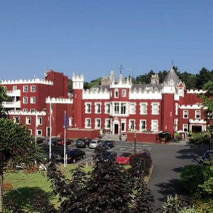 Parking lot and exterior of Fitzpatrick Castle Hotel in Dublin, Ireland on a bright sunny day