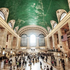 Busy blurred travellers in Grand Central Station terminal with light coming through the windows and green ceiling above.