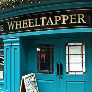 The exterior of Wheeltapper bar painted in blue with Christmas reef and lights.