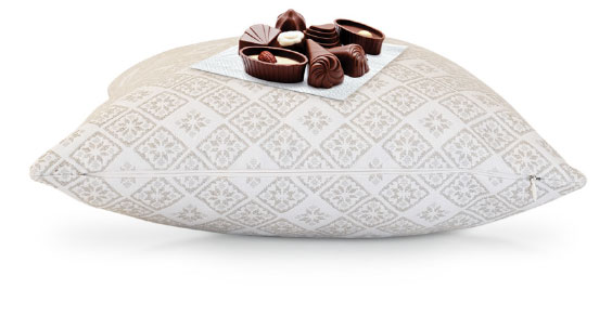 Luxury dark chocolate on a napkin placed on top of a patterned cushion