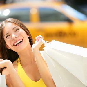 Happy woman wearing a yellow shirt carrying shopping bags with a blurred yellow taxi cab in the background