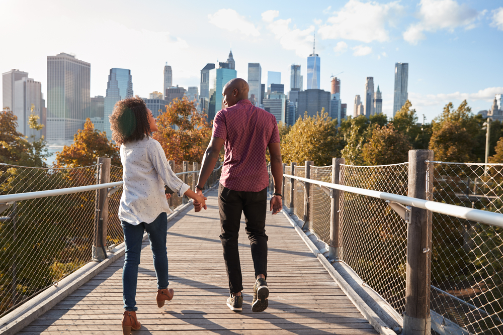 Happy couple holding hands walking over a bride with New York city skyline in front of them