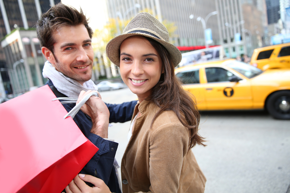 Smiling happy couple in front of yellow taxi cab with shopping bags