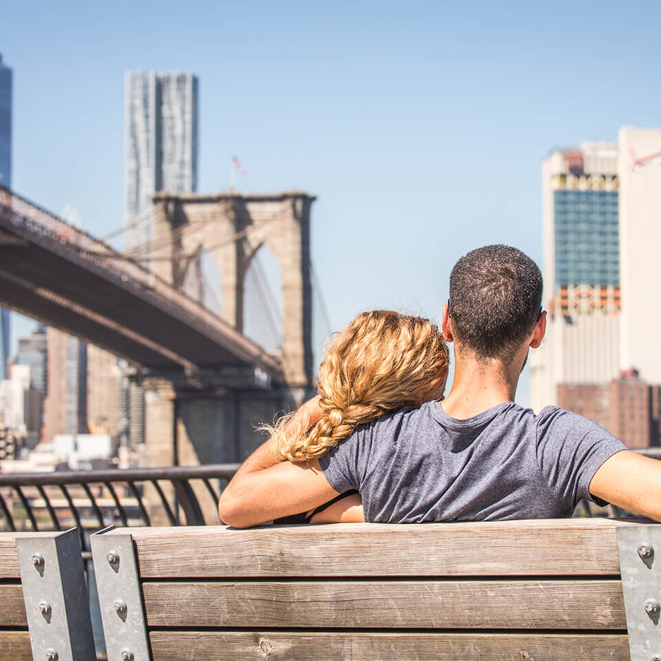 Happy couple sitting on bench on a bright sunny day admiring Brooklyn Bridge