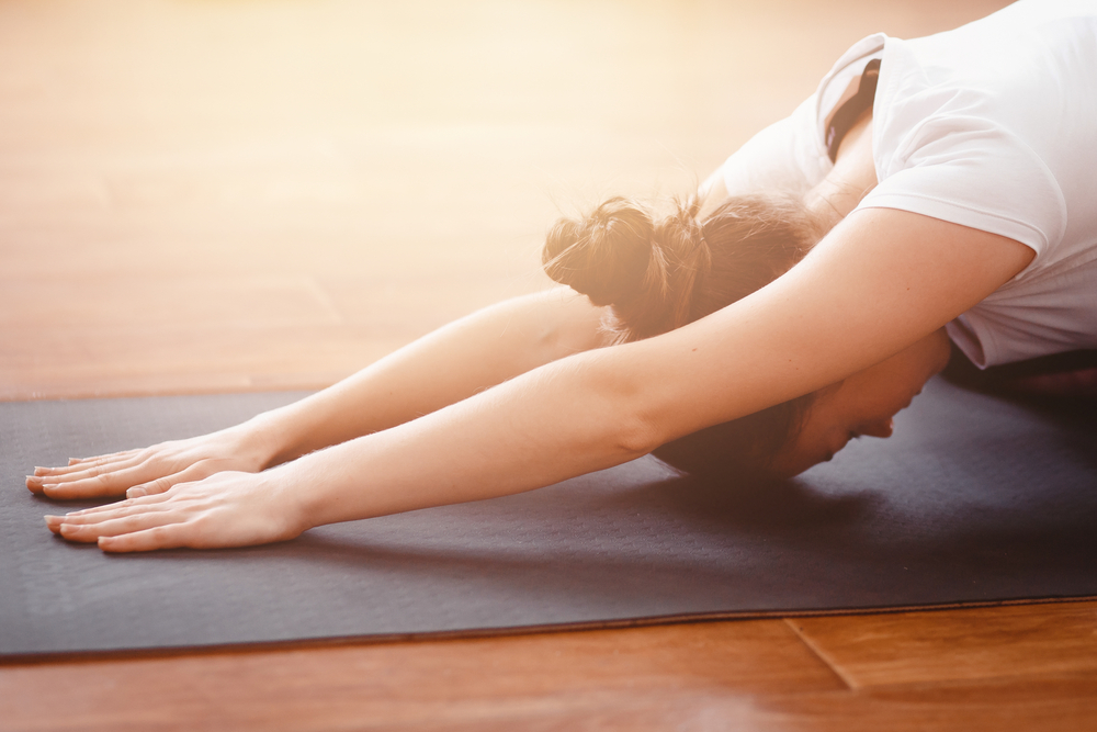 Women with arms and head in downward facing dog yoga position