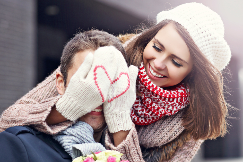 Woman with heart gloves hiding males face and smiling