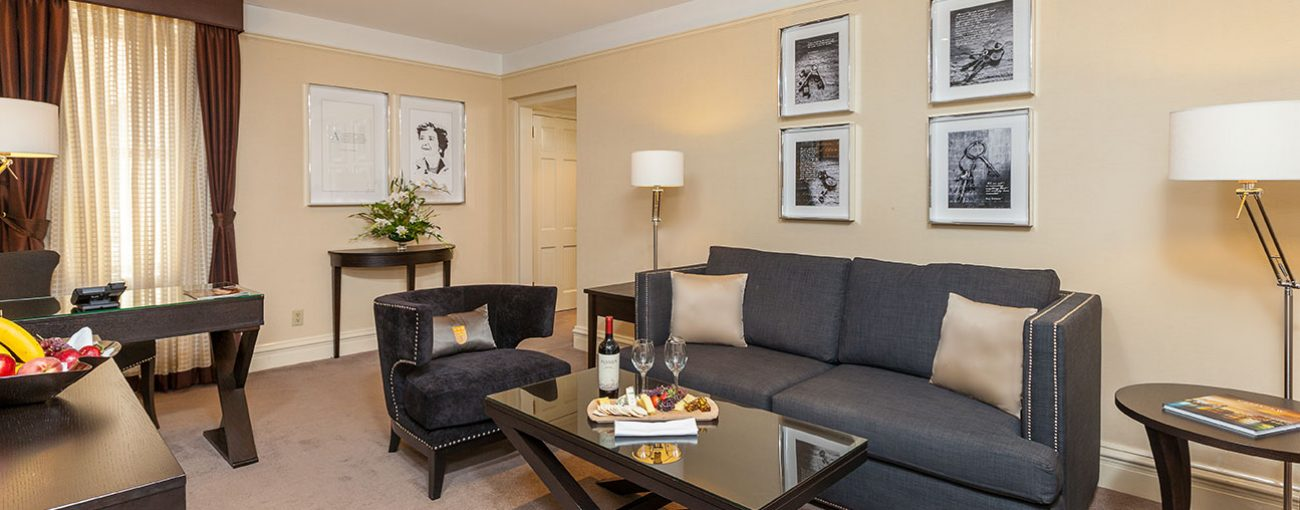 Grey couch and dark grey armchair with a cheeseboard and wine on a rectangular coffee table.