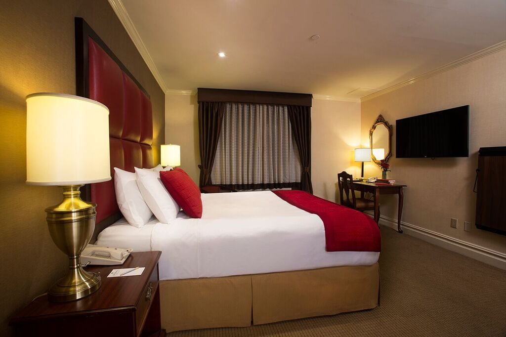 Double bedroom with white sheets, red leather headboard, side table and phone across from tv screen on wall and work desk.
