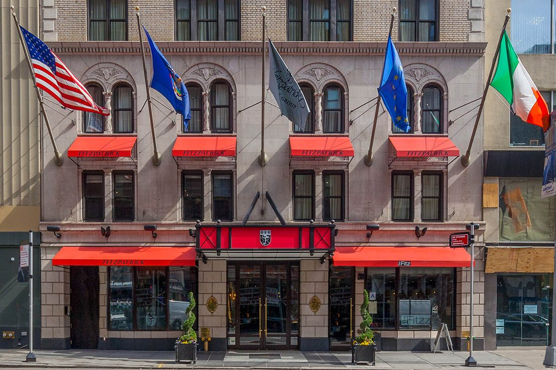 The exterior of The Fitzpatrick Hotel Manhattan with EU, United States and Fitzpatrick flags blowing in the wind.