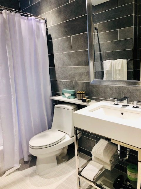 Black tiled bathroom with lilac shower curtain and white bathroom features