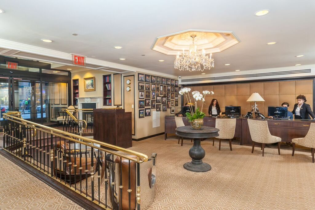 Fitzpatrick Hotels lobby with staff sitting at computers, brightly lit by a central chandelier abover tall flowers and a dark round table