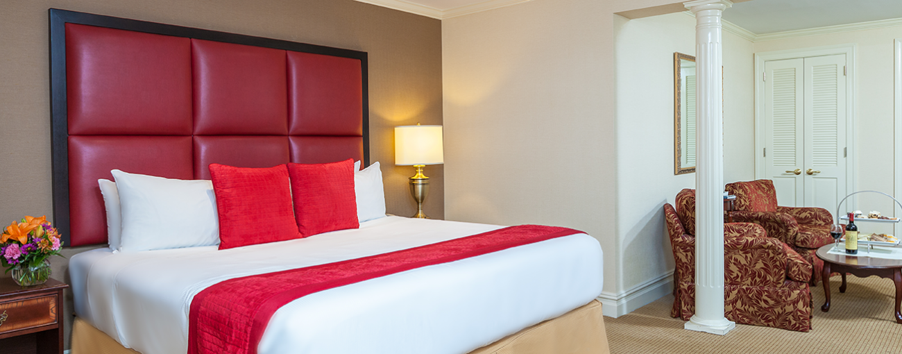 Fitzpatrick Deluxe Room with a bed, red accent pillows, leather headboard and breakfast with lit lamp on side table.