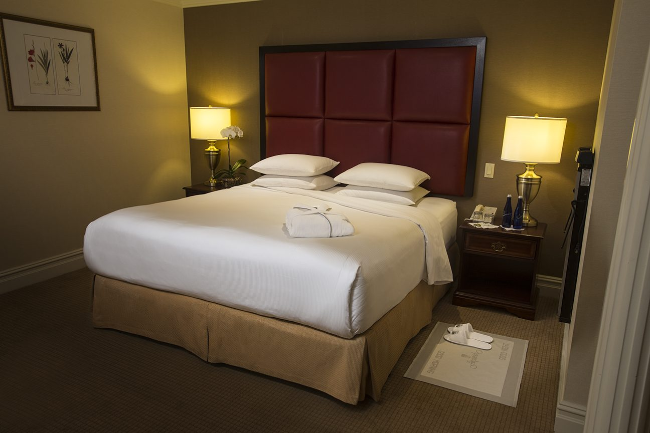 Bed with white sheets, folded robe, red leather headboard two side by side tables and lamps with white slippers on a mat.
