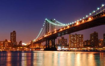 View of Manhattan bridge at night with lights on from East River in New York City below