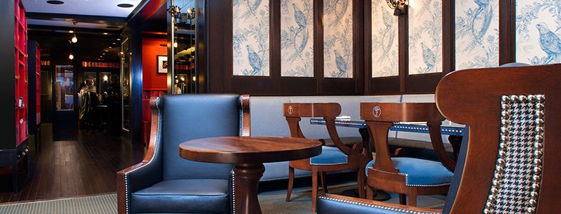 Dark wood tables and navy blue leather chairs in front of blue bird patterned wallpapered wall.