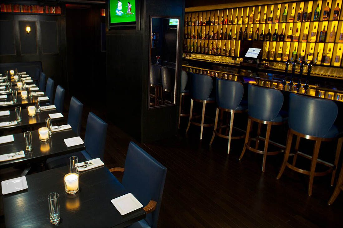 Navy leather bar stools, chairs and dark wood mirror in The Fitz Bar.