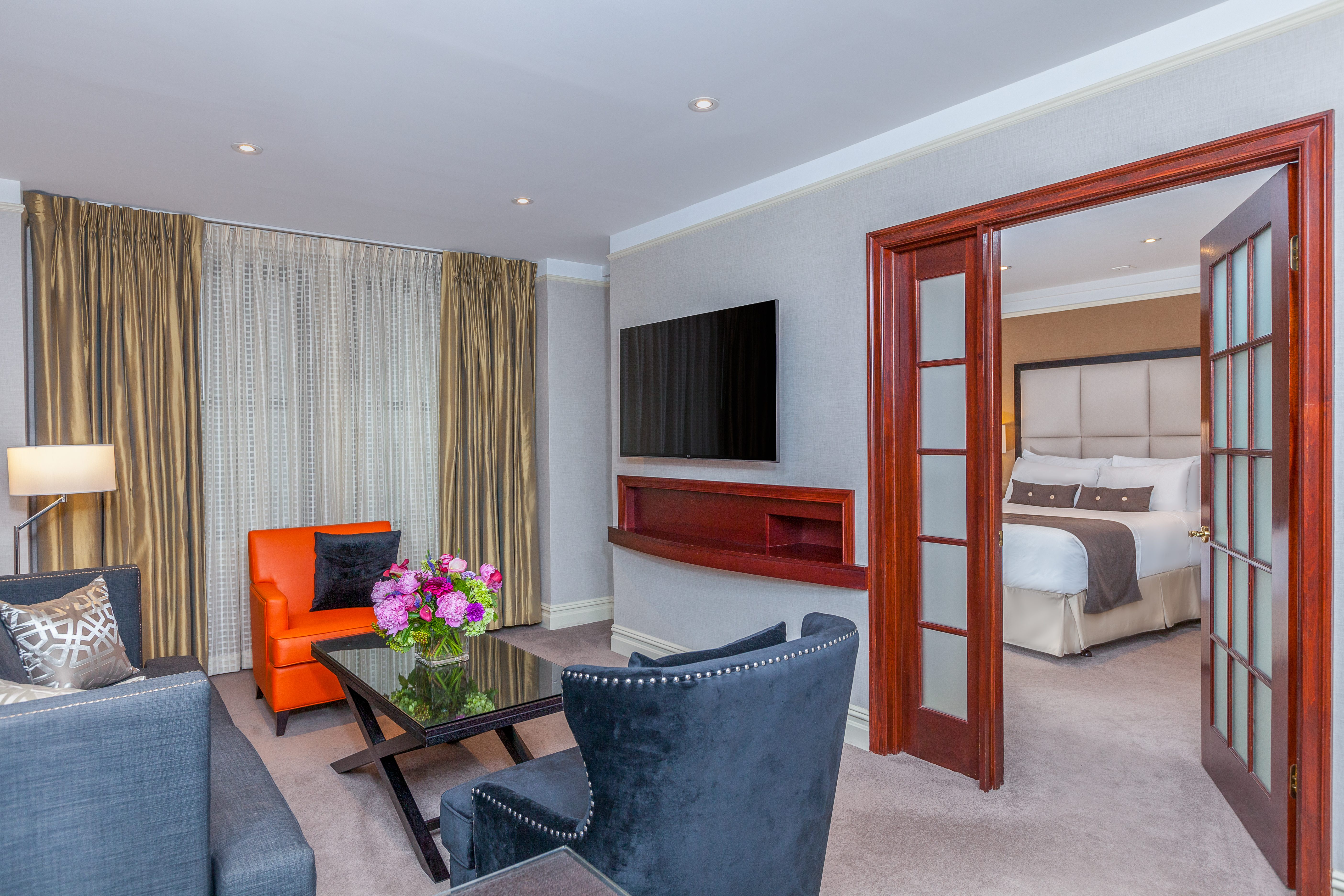 Seating area in a suite with orange armchair, grey armchair, dark coffee table, tv screen on the wall and door to the bedroom