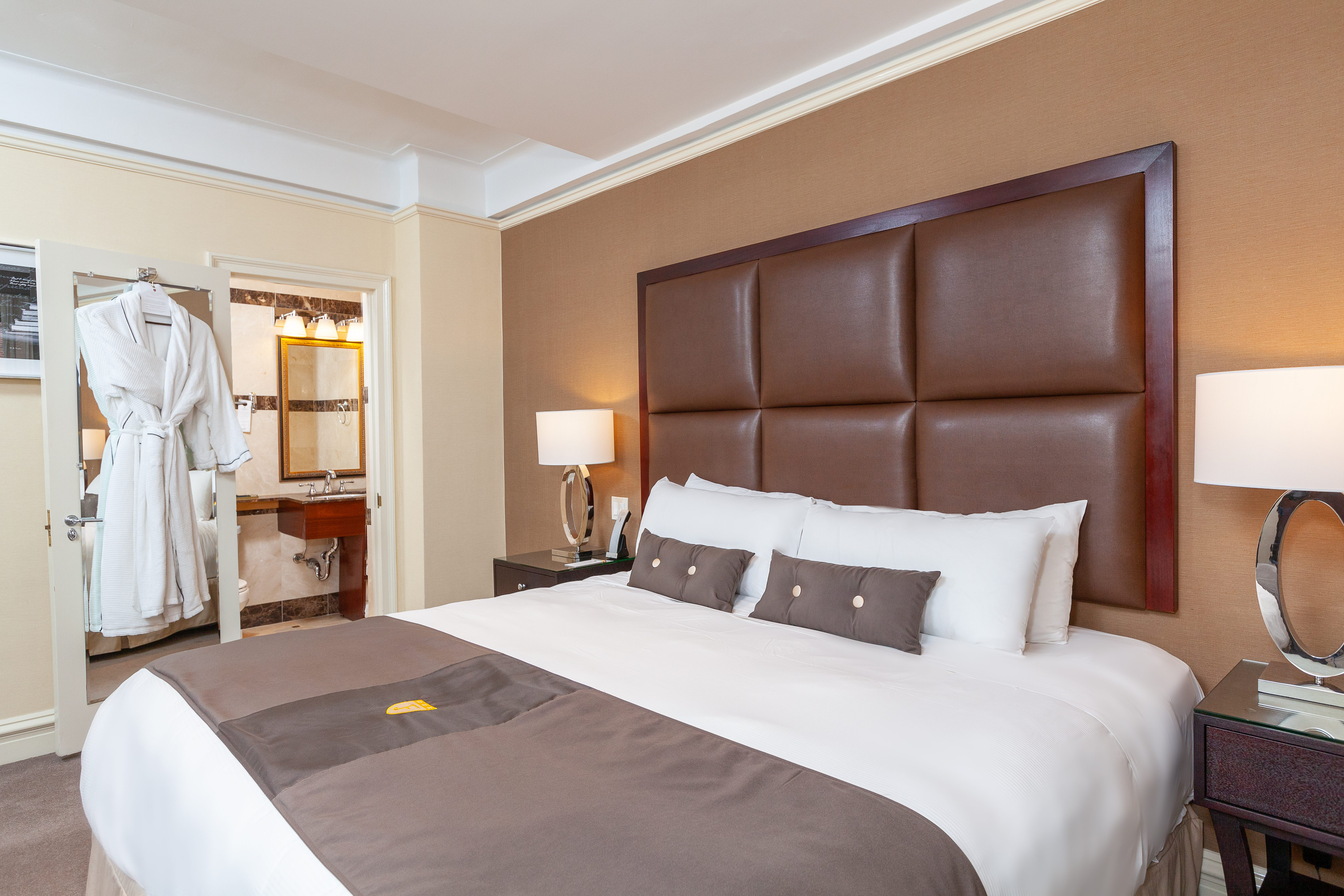 Double bed with two pillows, white sheets and chocolate leather headboard next to a side table and open door to the bathroom