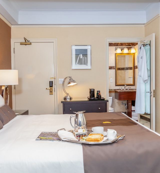 Breakfast tray with toast and warm beverages on bed, robes hanging in front of bathroom door