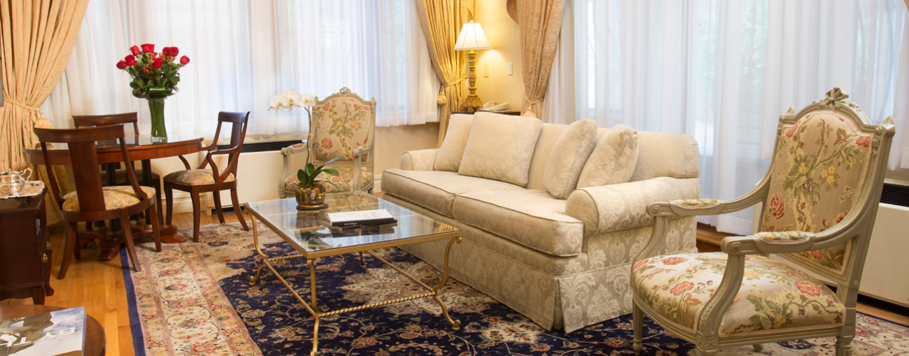 Brightly lit Penthouse suite with cream colored curtains and couch, glass coffee table and floral patterned chair.
