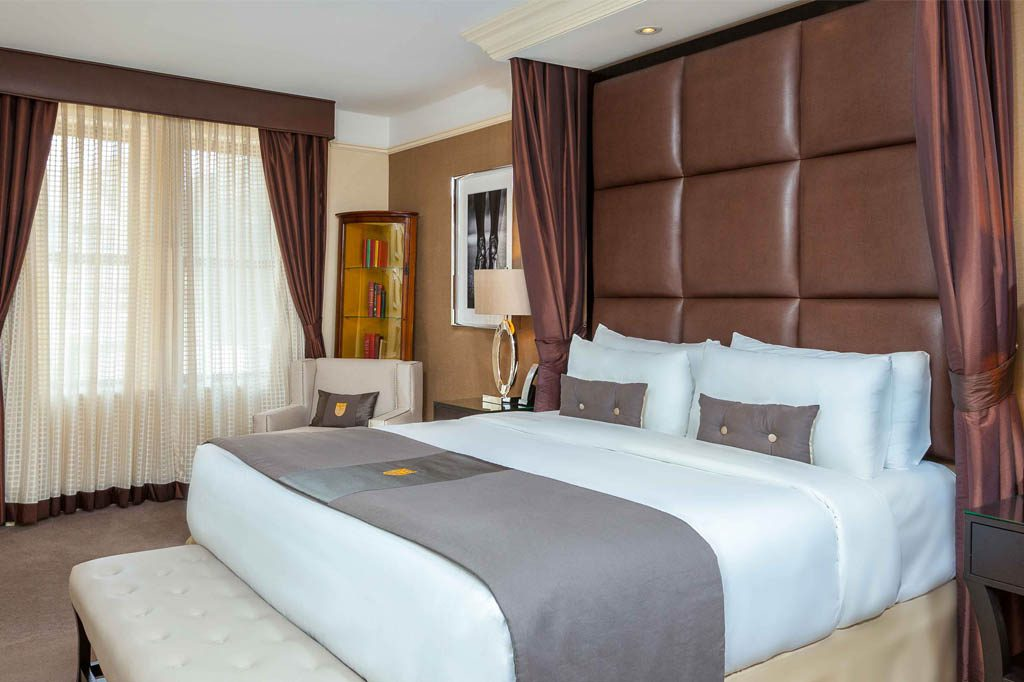 Bed with two pillows a throw, white sheets and chocolate leather headboard next to an armchair with a mini bookcase behind it