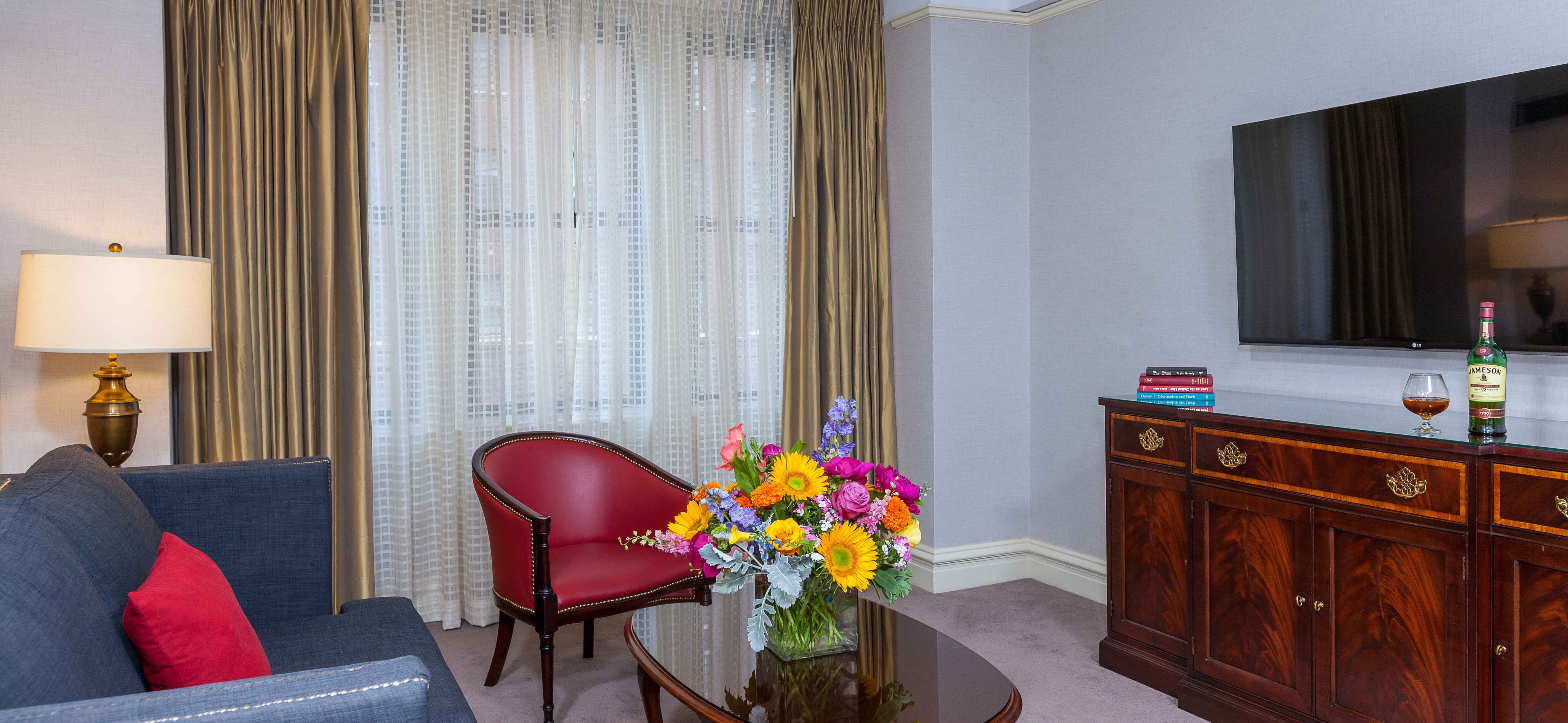 Lone red studded armchair in front of white and gold curtains with a floral bouquet on an oval coffee table.