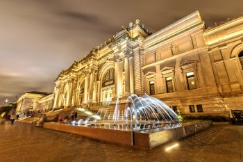Exterior of the Met Museum with fountain and exterior lights on