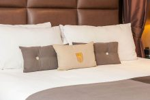 Fitzpatrick Hotels monogramed pillow on bed with chocolate leather headboard and white and brown pillows.