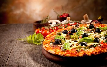 Italian style pizza with olives, cheese, sauce and mushroom toppings