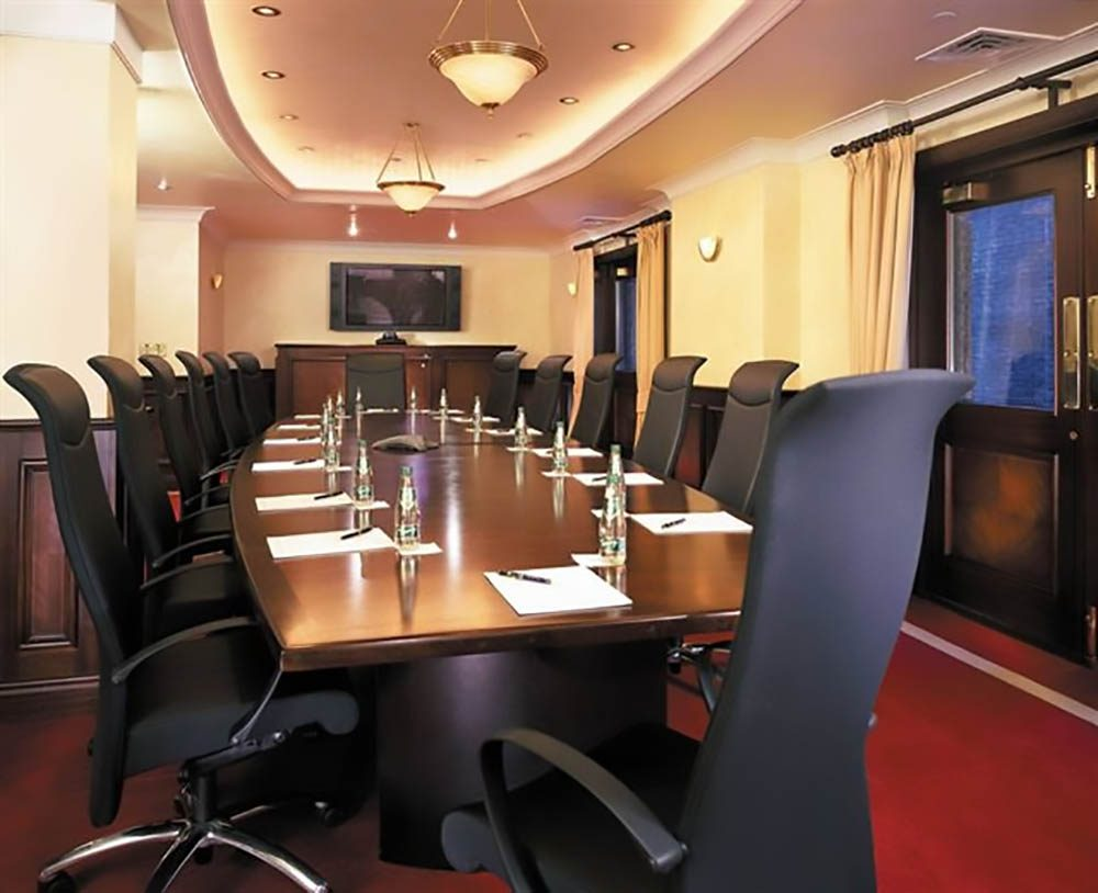 Fitzpatrick Manhattan Hotel boardroom table and chairs with a screen on the background wall.