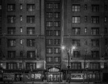 The exterior of Fitzpatrick Grand Central at night time in black and white.