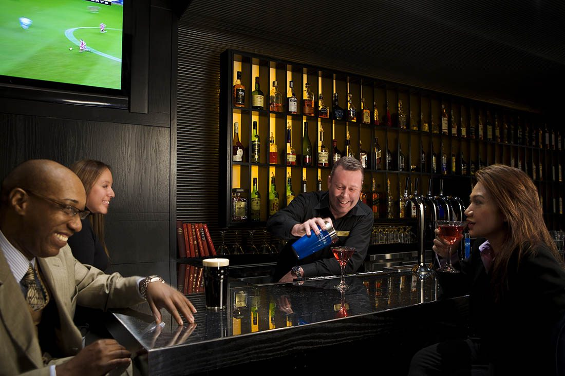 Barman at The Fitz, pouring red-hued alcohol from cocktail shaker into martini glass next to a pint of Guinness beer at the bar.