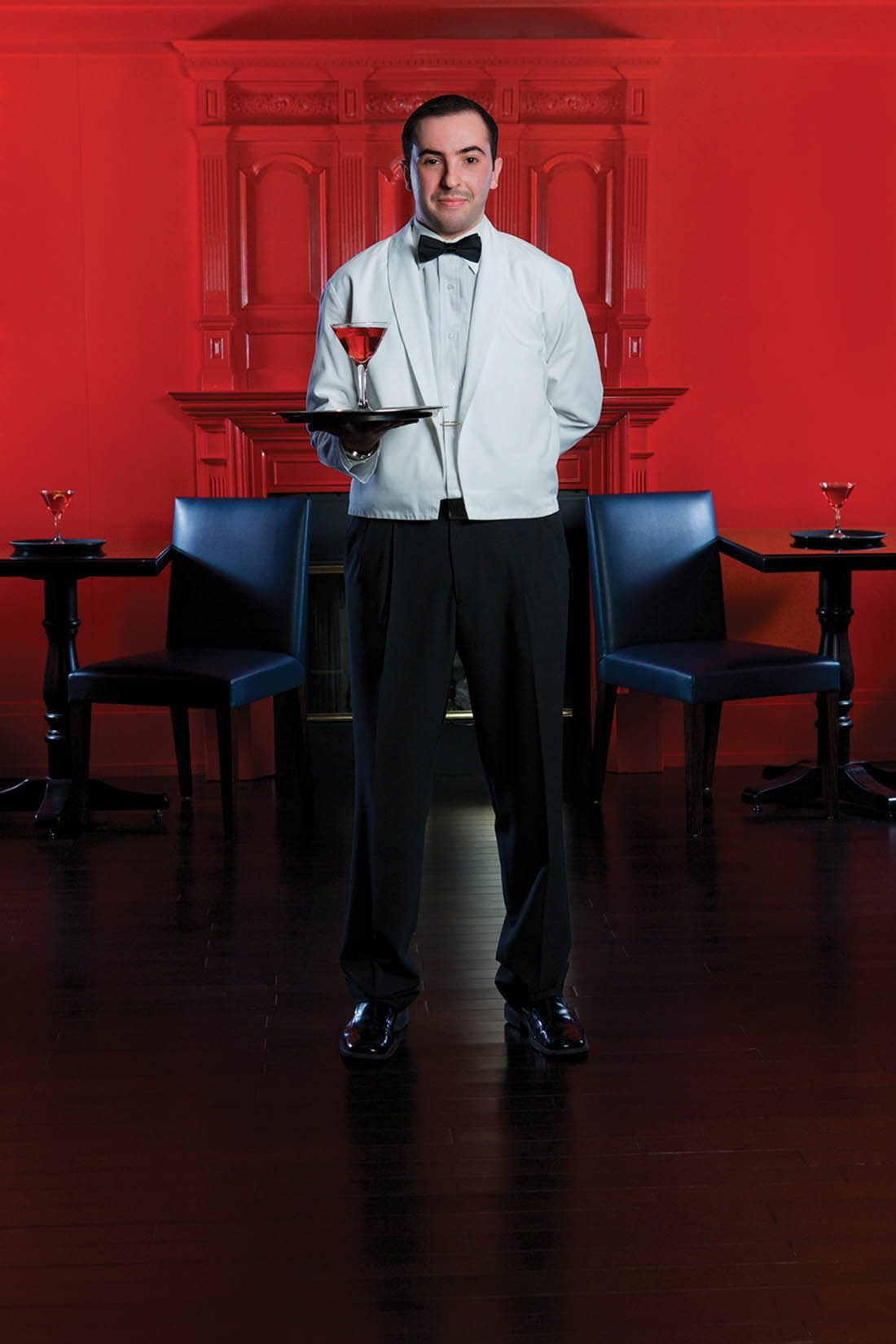 Bow-tied waiter holding a tray with a serving of alcohol in front of a red wall and two navy blue chairs on either side.