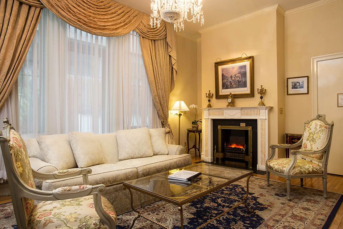 Brightly lit Penthouse suite with cream colored curtains and couch, glass coffee table and gold ornate clock above a lit fireplace.