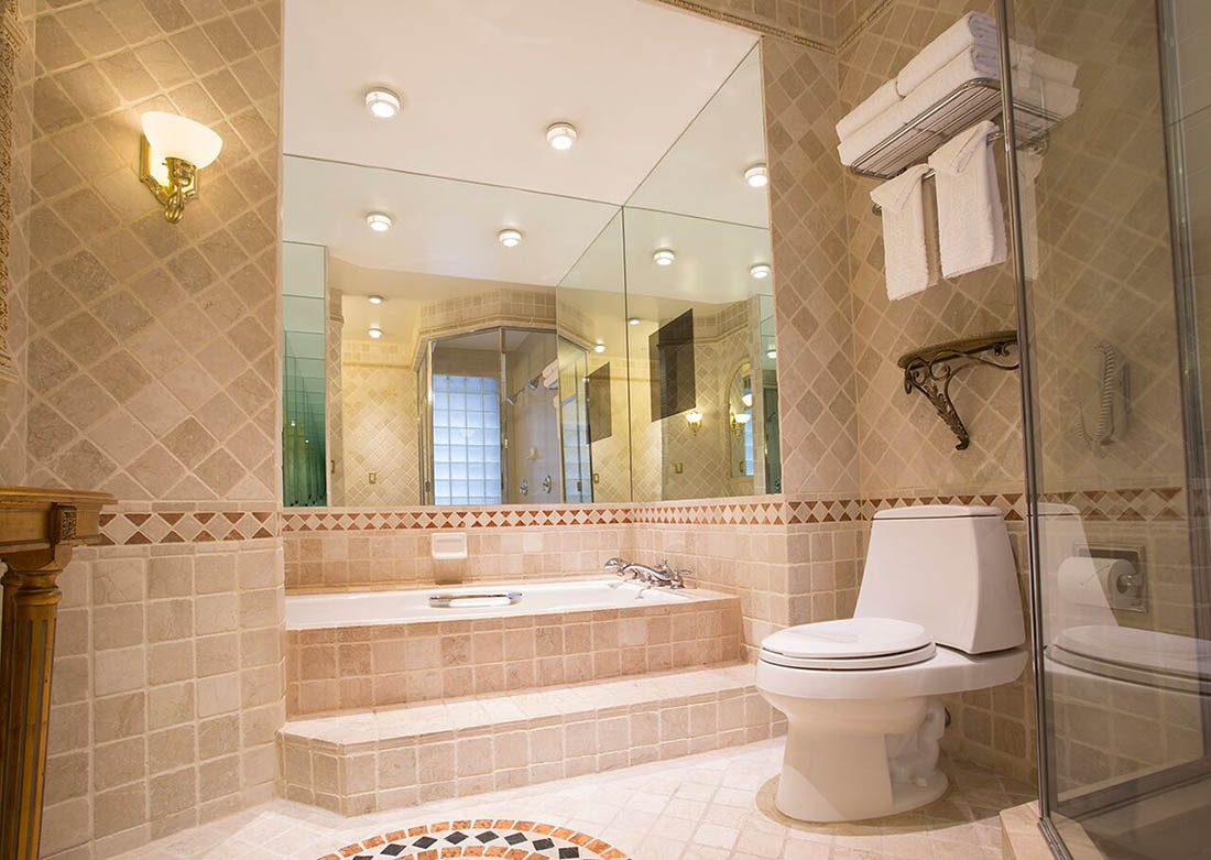 Brightly lit tiled bathroom with steps leading to a large tub, folded white towels on the top shelf above a toilet on the left