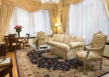 Brightly lit Penthouse suite with cream colored curtains and couch, glass coffee table and twin floral patterned chair.