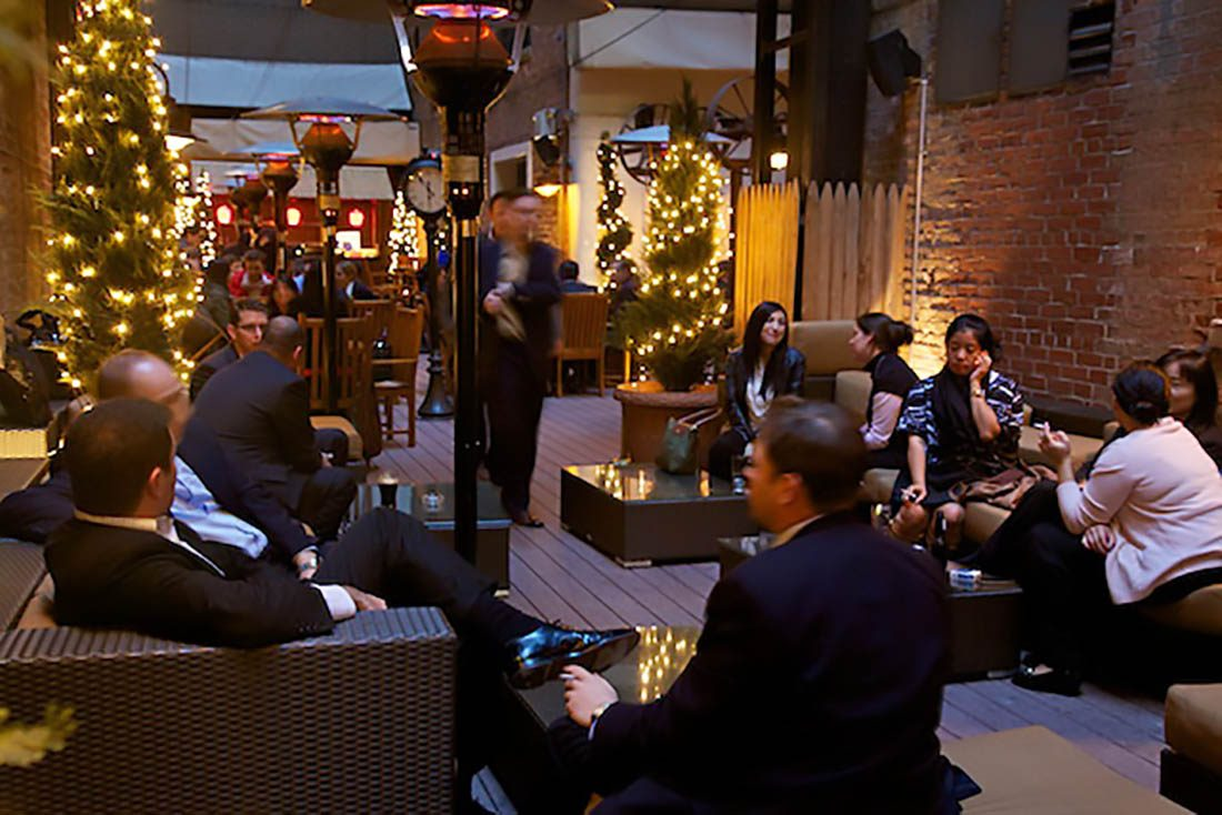 Guests at Wheeltapper in the evening amongst Christmas reef and lights decorated patio and outdoor standing heaters.