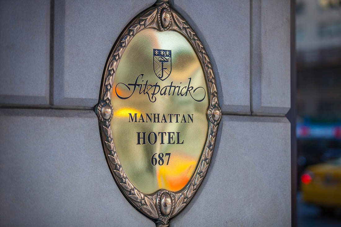 Fitzpatrick Manhattan Hotel golden plaque on building exterior.