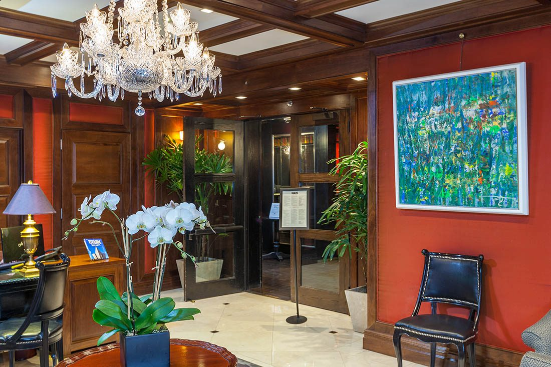 Chandelier in the top left corner of the hotel lobby with an open door, abstract art on wall, white orchids and black chair.