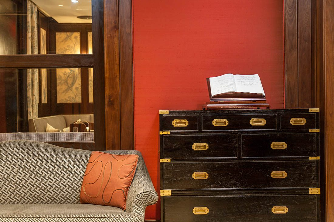 Black chest of drawers with a leather-bound book beside the arm of a patterned grey couch and orange patterned cushion.