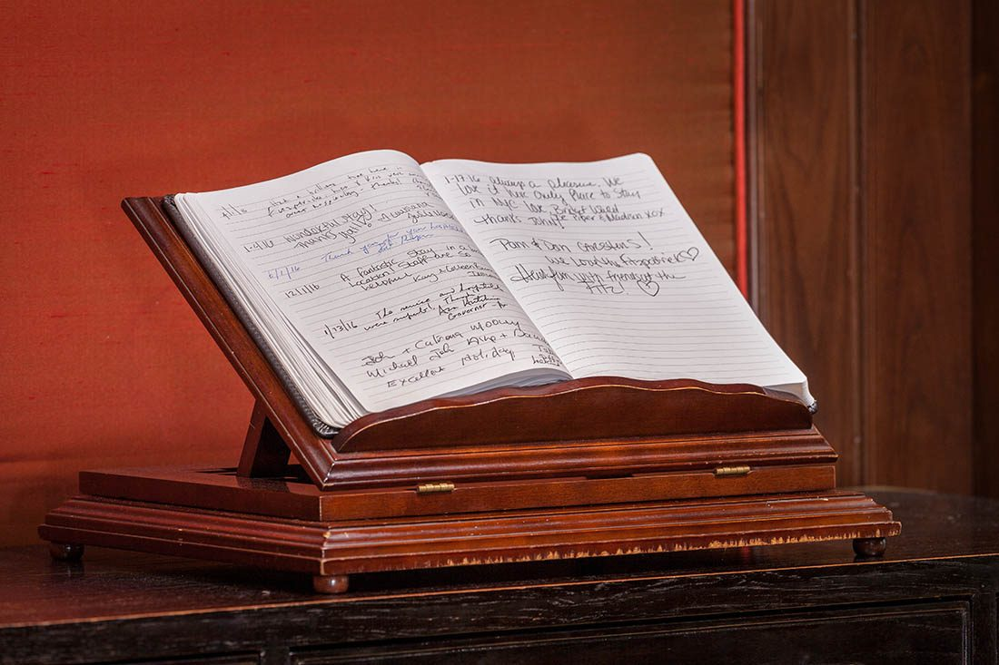Signatures from Fitzpatrick Hotel guests in leather bound book on wooden stand