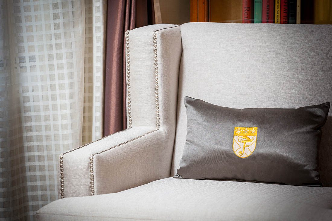 Fitzpatrick Hotels monogrammed cushion on a cream studded armchair next to the window.